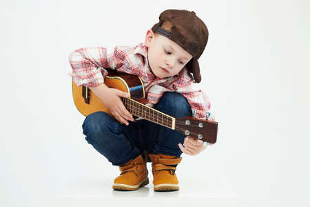 Foto de funny child boy with guitar.ukulele guitar. fashionable country boy playing music - Imagen libre de derechos