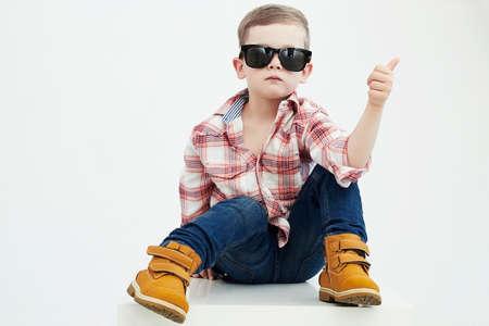 Foto de Funny child.fashionable little boy in sunglasses.stylish kid in yellow shoes - Imagen libre de derechos