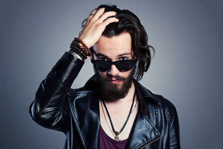 Photo pour young bearded man in a leather jacket. Hipster in sunglasses - image libre de droit