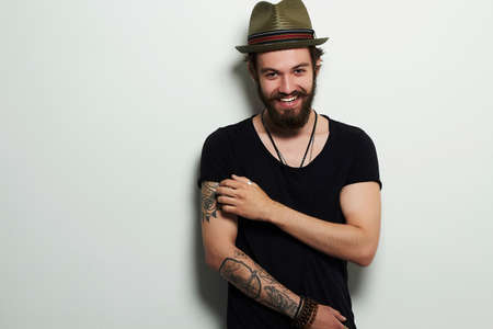 young man. Smiling Hipster boy.handsome man in hat.Brutal bearded boy with tattoo