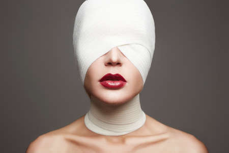 glamorous image for halloween.female face wrapped in bandage.beautiful girls lips.beauty make-up woman.plastic surgery