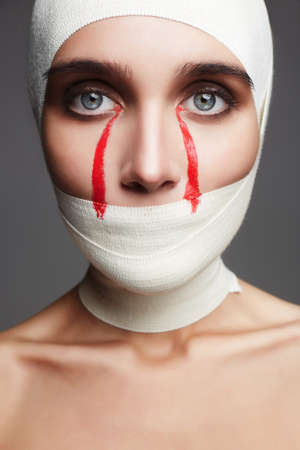 glamorous Halloween card.female face wrapped in bandage.girl with bloody tears.beauty make-up woman.plastic surgery