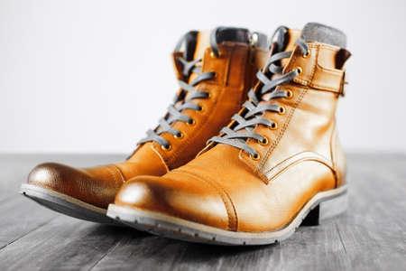 Foto de Yellow shoes. fashion men's boots. trendy shoes still life on wooden background - Imagen libre de derechos