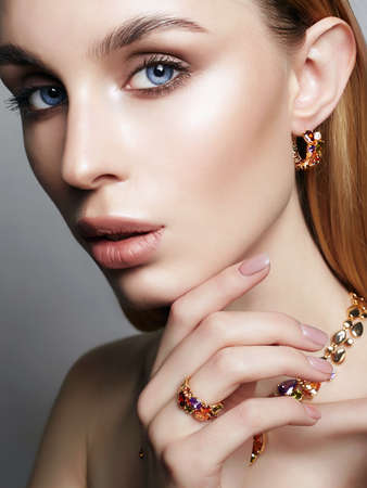 Photo pour Gold jewelry on beautiful girl. young blonde woman with make-up and jewels accessories. Beauty Fashion Portrait - image libre de droit