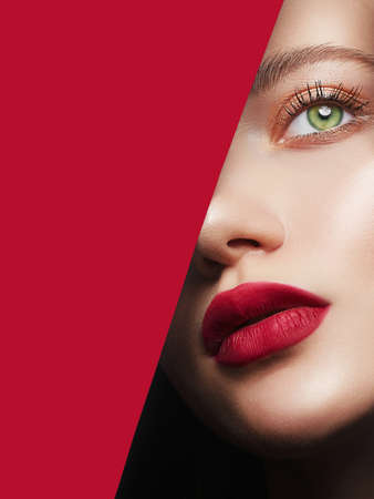 Photo for beautiful woman with a makeup, into the hole of red paper. make-up artist concept. beauty girl with beautiful bright green eyes and red Lips - Royalty Free Image