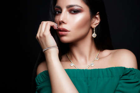 Photo pour Beautiful brunette Girl in Jewelry and green dress. Young Woman with Make-up and accessories - image libre de droit