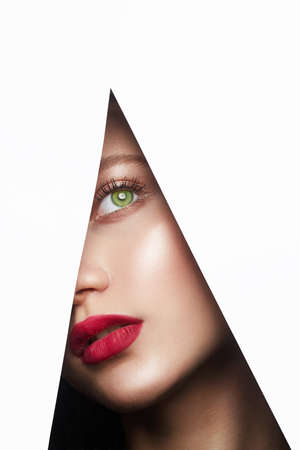 Photo for young beautiful woman. female face with makeup into paper hole. make-up artist concept. arrows on the eyes. - Royalty Free Image