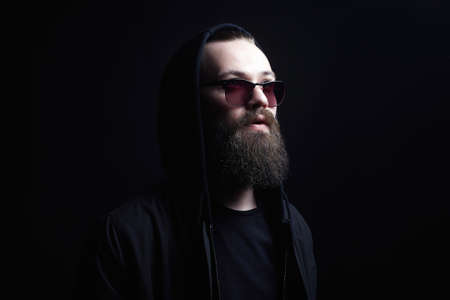 Photo pour Handsome Man in Hood and sunglasses. Boy in a hoodie. portrait of bearded man - image libre de droit