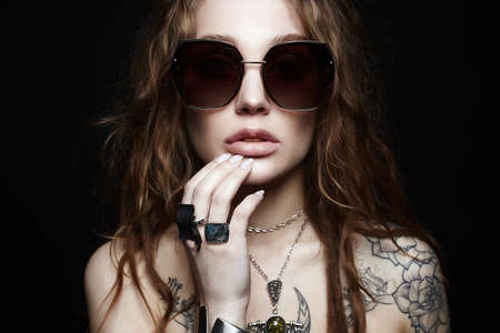 Photo pour fashion portrait of Beautiful sexy woman with tattoo. beauty tattooed girl in sunglasses and jewelry - image libre de droit