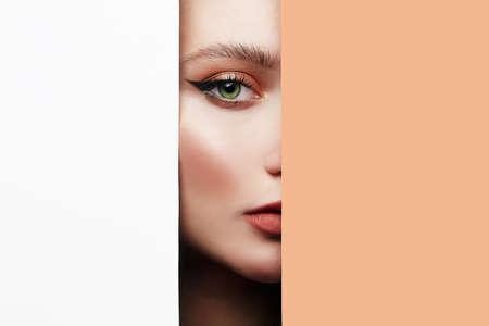Photo pour young beautiful woman. female face with makeup into paper hole. make-up artist concept. arrows on the eyes. - image libre de droit