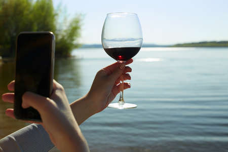 Photo for girl photographs a glass of wine in her handon smartphone. Female hand with Wine on Nature - Royalty Free Image