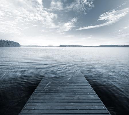Old wooden pier goes under deep blue water  Monochrome photo