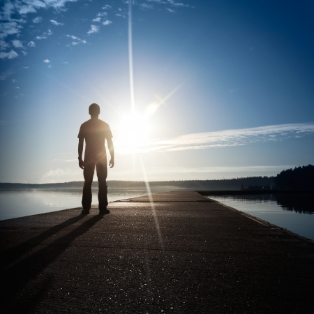 A man stands on the concrete pier starring at the setting Sun