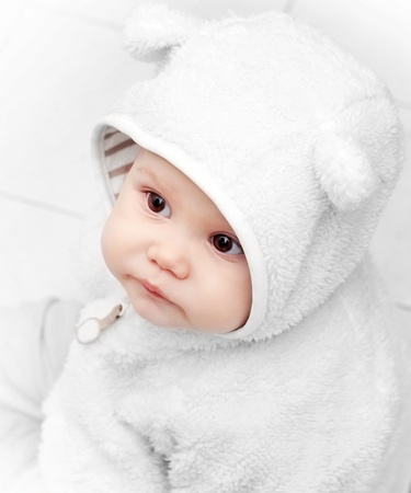 little baby in white bear costume on white background