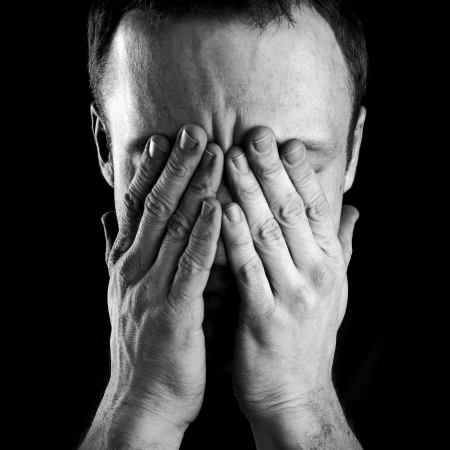 Monochrome portrait of young stressed Caucasian man covers his face with hands isolated on black background