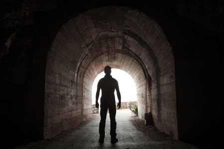 Young man stands in dark tunnel and looks out in the glowing end
