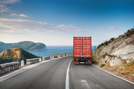 Foto de Cargo truck on the mountain highway with blue sky and sea on a background - Imagen libre de derechos