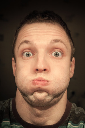 Young funny Caucasian man inflates cheeks. Closeup portrait