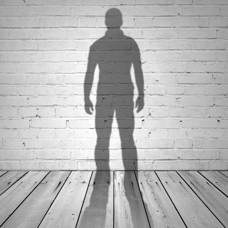 Shadow of a man on white brick wall and wooden floor