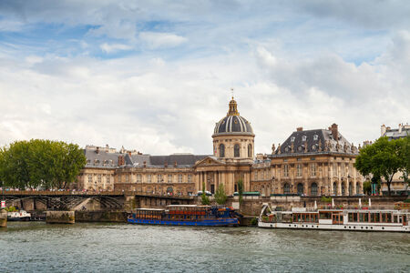 Paris, France - August 07, 2014: Seine river coast with Facade of Institute de France in Paris. Architect Louis Le Vau, was made between 1662 and 1688