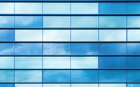 Modern office building wall made of blue glass and steel frame, background texture
