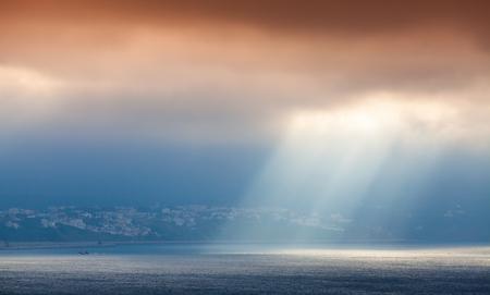 Volume sunlight goes through dark orange clouds. Bay of Tangier, Morocco, Africa