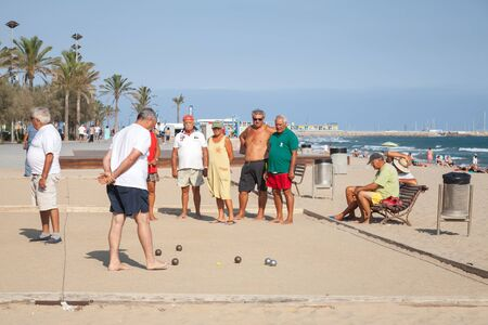Calafell, Spain - August 20, 2014: Seniors Spaniards play Bocce on a sandy beach in Calafell, resort town in Catalonia