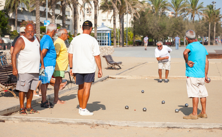 Calafell, Spain - August 20, 2014: Seniors Spaniards play Bocce on sandy beach in Calafell, small resort town in Catalonia