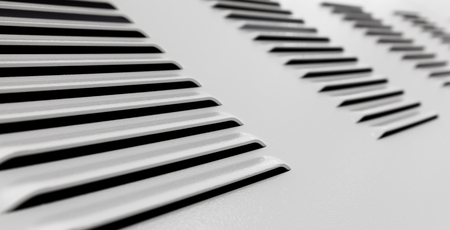 White metal industrial wall with ventilation grille, closeup photo with selective focus and shallow DOF