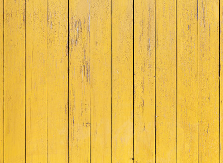 Old yellow wooden wall with cracked paint layer, detailed background photo texture