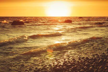 Photo pour Baltic sea coastal landscape at sunset with stormy shore water and stones. Warm tonal correction filter - image libre de droit