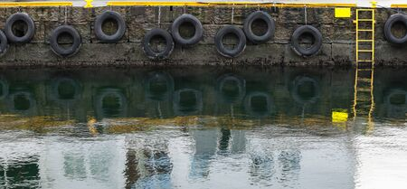 Photo for Grungy concrete mooring wall with hanging tires as bumpers, background photo texture - Royalty Free Image