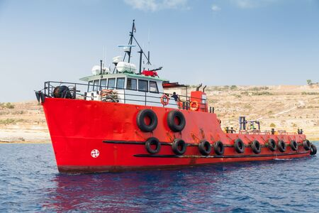 Photo for Tug boat with bright red hull goes near  Malta island at sunny day - Royalty Free Image
