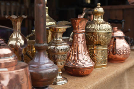 Photo pour Assortment of stylized Oriental copper dishware standing on a counter of a gift shop in Jordan - image libre de droit