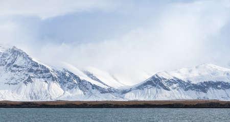 Photo pour Icelandic landscape with coastal snowy mountains under cloudy sky. Reykjavik, Iceland - image libre de droit