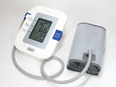A modern blood pressure monitor and cuff  On white