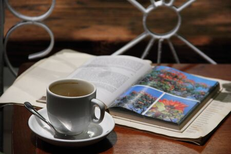 Cup of coffee with an open book