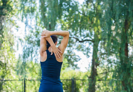 Athletic girl working out in a park. Beautiful embossed back. Health and Sports