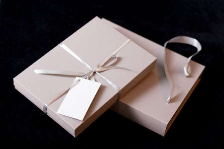 Foto für Beautiful packaging for gift in bed tones against the background of a Christmas tree with golden lights. Holidays content 2020 - Lizenzfreies Bild