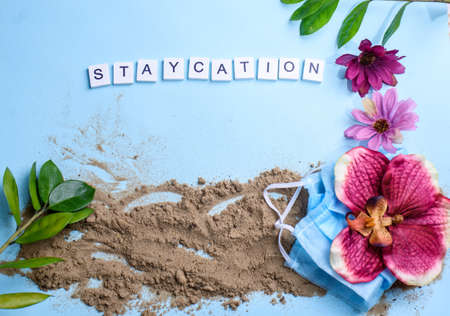 Photo pour Beach sand on a blue background with wood letters and a word staycation. Holiday at home - image libre de droit