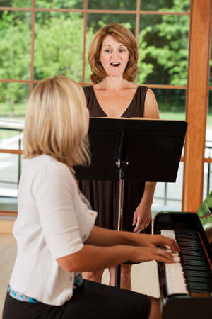 Mature woman taking singing voice lessons with teacher at the piano