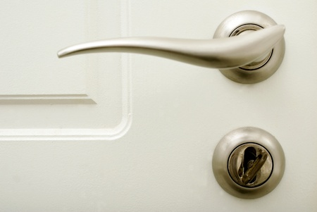 white house door with stainless door handle and lock with key