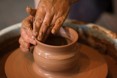 Photo pour Rotating potter's wheel and clay ware on it taken from above. A sculpts his hands with a clay cup on a potter's wheel. Hands in clay. Process of. Side view - image libre de droit
