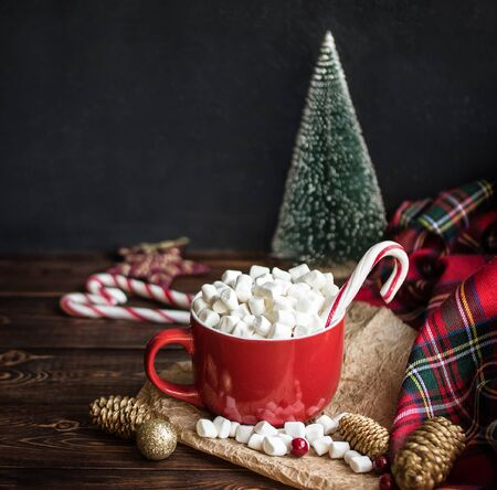 Cappuccino with marshmallow in red mugs and  striped stick candys, fir cones on wooden table. Christmas holiday mood concept. Cozy Winter background
