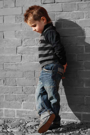 little boy on a background a brick wall