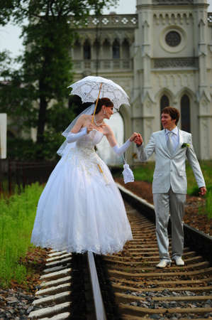 Photo for Newly-married couple walking on rails - Royalty Free Image