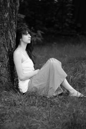 thinking girl sitting near tree