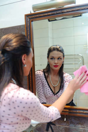 woman wash the mirror and looking into it