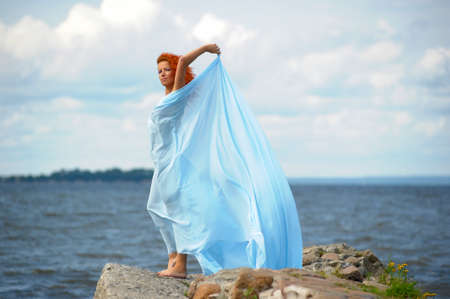 young woman standing on a promontory and enjoying the wind
