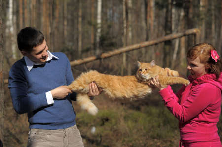 Young couple spends time playing with their pet cat